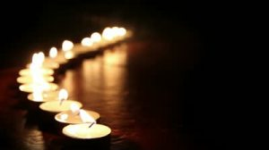 stock-footage-candlelight-little-candles-lined-up-light-up-one-by-one